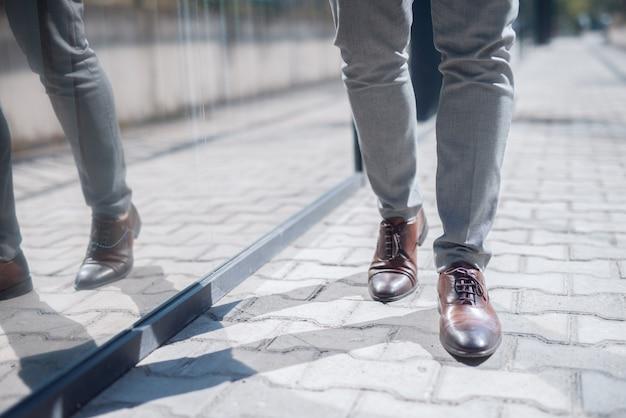 実業家の歩行の足を閉じます。ストリート外観。