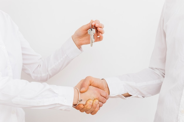Close-up of businessman shaking hand while giving keys on white background