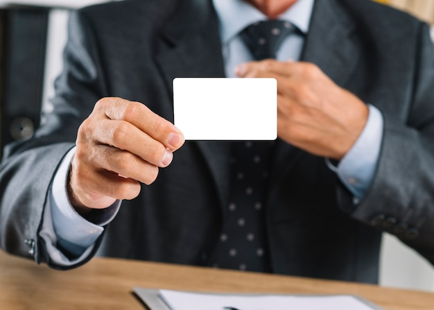 Close-up of businessman showing blank white visiting card
