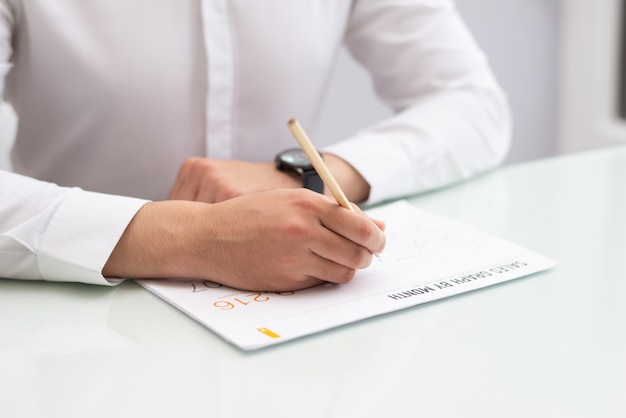 Close-up of businessman sitting at table and writing on paper