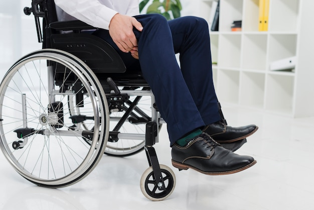 Close-up of a businessman sitting on wheelchair suffering from the leg pain