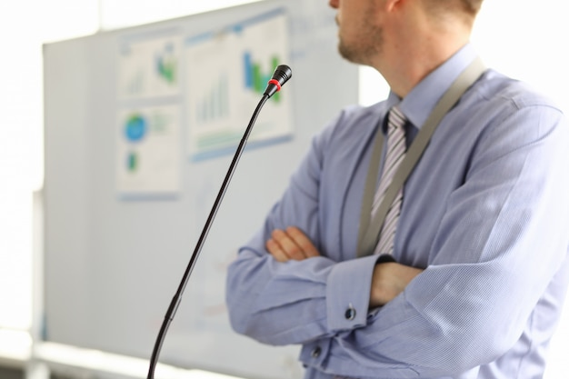 Close-up of businessman speaking about financial statement into microphone to partners and workers. male person at seminar. business conference and company concept