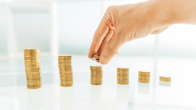 Закройте вверх. бизнесмен, укладывая монеты на офисный стол. фото с копией пространства