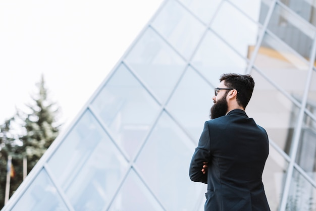Close-up of a businessman standing in front of corporate building