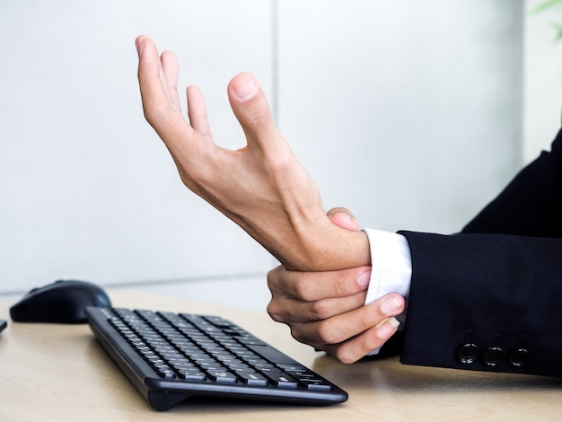 Close-up businessman in suit getting hand pain while using notebook computer in office