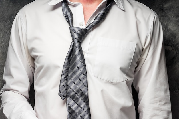 Close up of businessman taking off his tie on gray grunge background