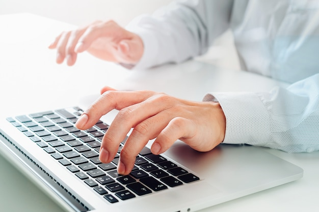 Close up of businessman typing keyboard with laptop computer on white desk in modern office