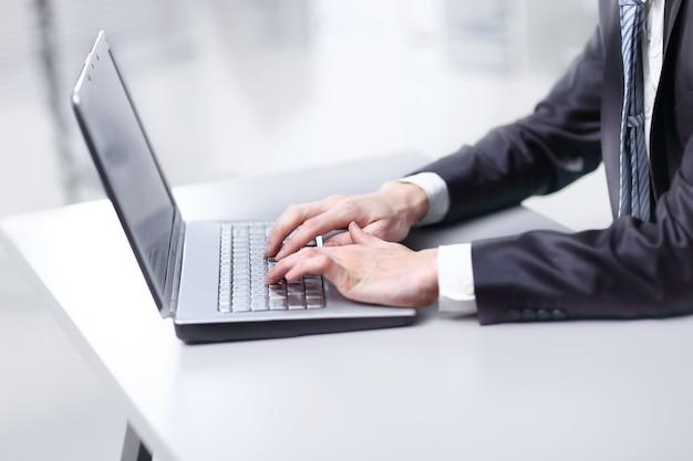 閉じる。ラップトップで入力するビジネスマン。人とテクノロジー。