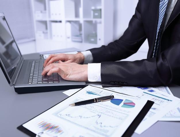 閉じる。ビジネスマンはラップトップを使用して財務データをチェックします。