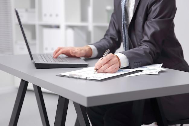 閉じる。ビジネスマンはラップトップを使用して財務グラフィックをテストします。