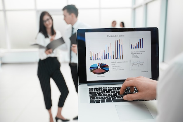 Close up.businessman은 사무실 로비에 서 있는 동안 노트북을 사용합니다. 사람과 기술