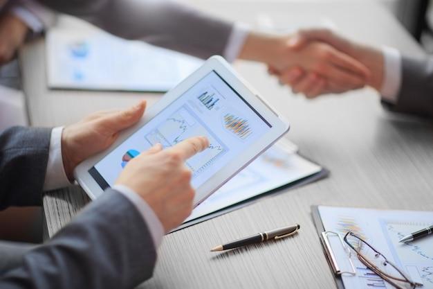 閉じる。財務データを分析するためにデジタルタブレットを使用しているビジネスマン。ビジネスコンセプト。