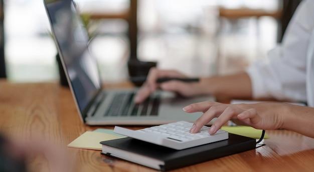 Крупным планом бизнесмен, использующий калькулятор и ноутбук для расчета финансов, налогов, бухгалтерского учета, статистики и концепции аналитических исследований