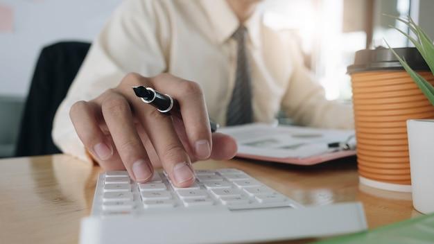 Крупным планом бизнесмен, используя калькулятор и ноутбук для математических финансов на деревянном столе в офисе