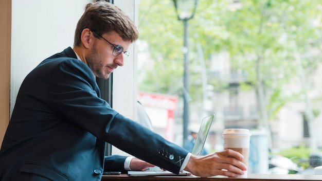 Close-up of a businessman using laptop holding disposable coffee cup in cafe