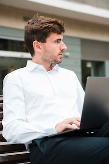 Close-up of businessman using on laptop looking away