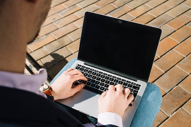 Close up of businessman using laptop outdoors