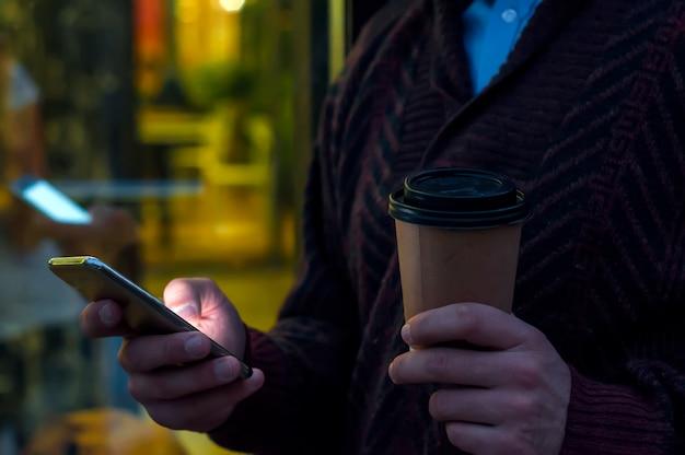 Primo piano di un uomo d'affari utilizzando il telefono cellulare e tenendo tazza di carta. close-up dettaglio di un businessmans mano azienda tazza di carta e utilizzando uno smartphone, mentre camminando sulla strada.
