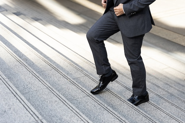 Close up businessman walking stepping up on business district urban, business concept