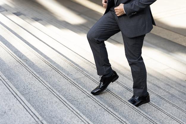 ビジネス地区の都市、ビジネスコンセプトをステップアップ歩くビジネスマンをクローズアップ