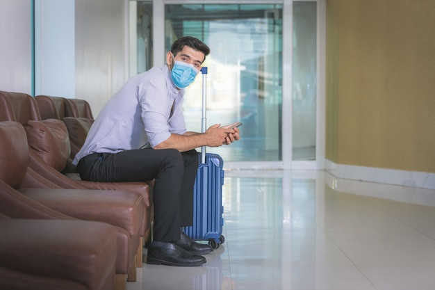 Close up businessman wearing face mask sitting alone at lobby of hotel.