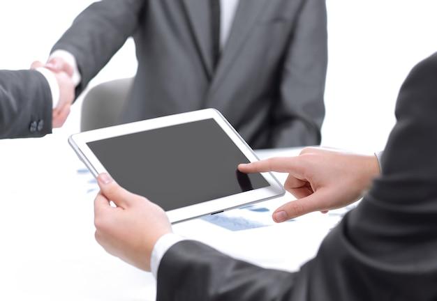 비즈니스 파트너의 악수를 배경으로 디지털 태블릿을 사용하는 비즈니스맨을 닫습니다.