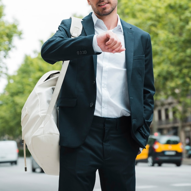 Close-up of a businessman with white backpack on his shoulder watching time on street