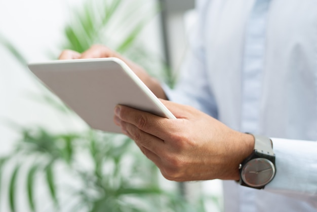Close-up of businessman with wristwatch using tablet