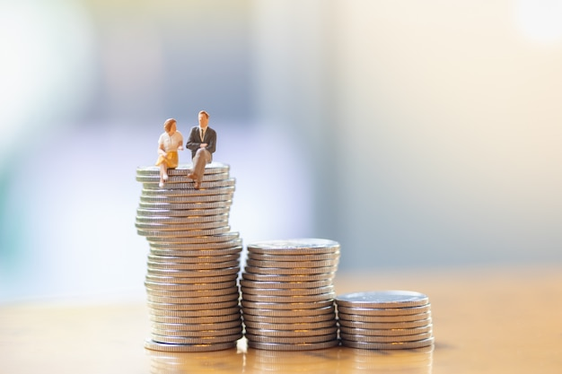 Close up of businessman and woman sitting and talking on top of stack of silver coins.