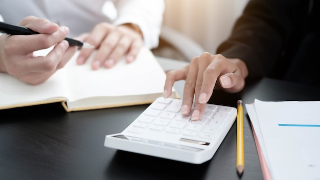 Close up businessman and woman using calculator and writing on a notebook in the office