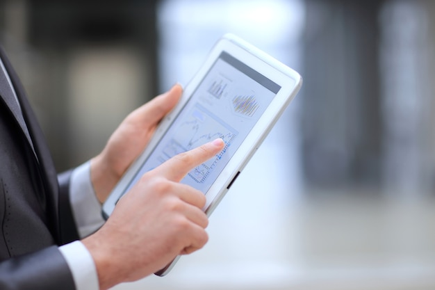 Закройте вверх. бизнесмен, работающий на цифровом планшете с финансовыми