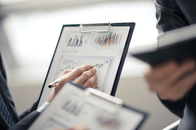 オフィスでグラフデータを扱うビジネスマンを閉じます。