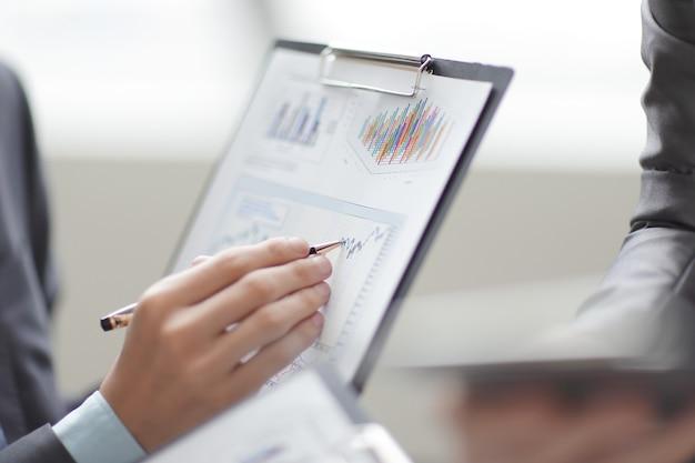 Закройте вверх по бизнесмену, работающему с данными графика в офисе.