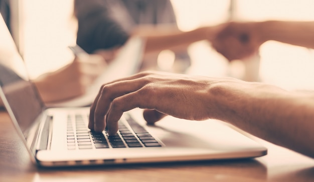 확대. 사업가 사무실 책상에 앉아있는 동안 노트북에서 작동합니다. 비즈니스 개념입니다.
