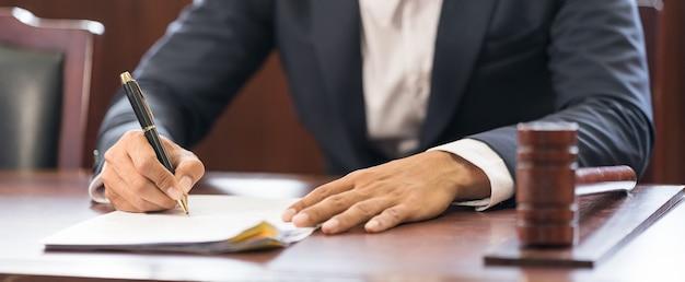 クローズアップビジネスマンはレポート用紙に書き込みます