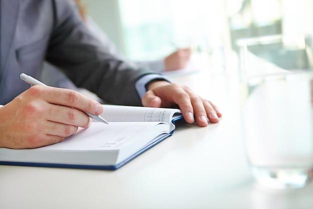 Close-up of businessman writing an idea