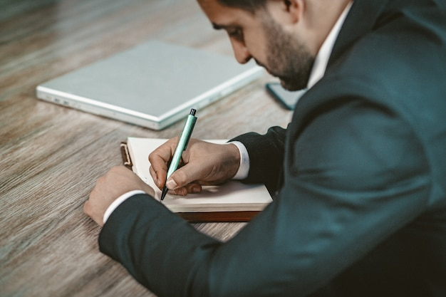 Close up of businessman writing in notebook