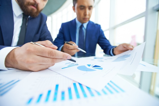 Close-up businessmen working together with diagrams