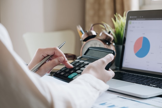 Close up of businesswoman or accountant hand holding pen working on calculator