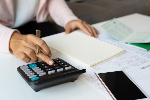 Close up of businesswoman calculating monthy expense at her desk. home saving concept. financial and installment payment concept.