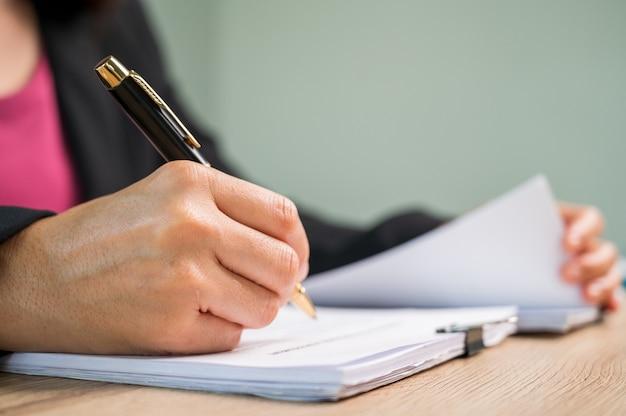 Закрыть вверх бизнесвумен рука подписать контракт документ на рабочий стол в деловом офисе