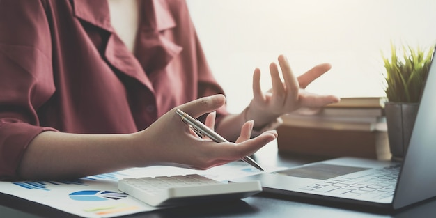 Close up businesswoman hands gesturing with laptop, calculator and graphs on her office table