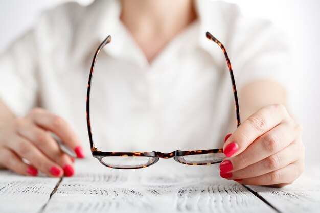 Close-up of businesswoman hands holding eyeglasses