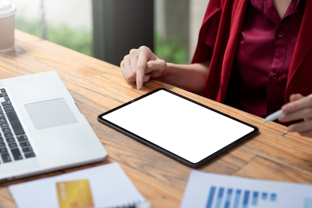 Close-up of businesswoman holding a pen using tablet blank white screen chart profit expenses at the office.