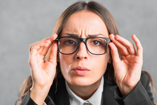 Close-up of businesswoman looking curiously through black eyeglasses