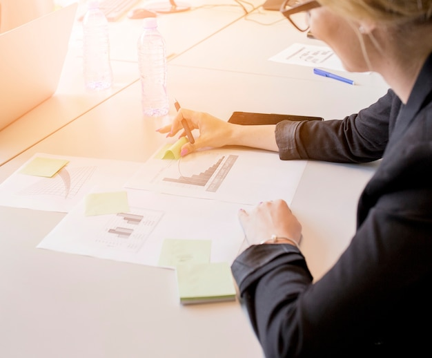 Close-up of businesswoman looking at sticky notes on graph