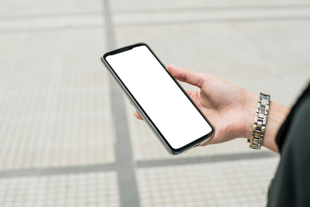 Close-up of businesswoman's hand holding smartphone displaying white screen