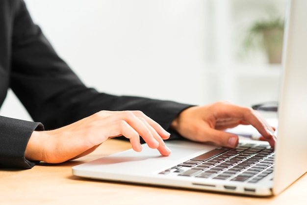Close-up of businesswoman's hand typing on laptop over desk