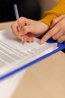 Close up of businesswoman signing investment papers contract with confident partner sitting at desk in startup company