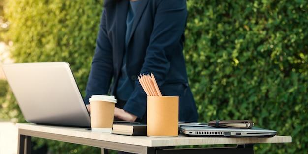 Close-up di imprenditrice digitando documenti sulla tastiera del computer portatile tenere tazza di caffè e uomini d'affari che lavorano a sfondo. vista selettiva. effetto del film e effetto sun glare